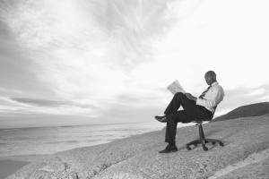 Businessman sitting in desk chair on beach reading paper
